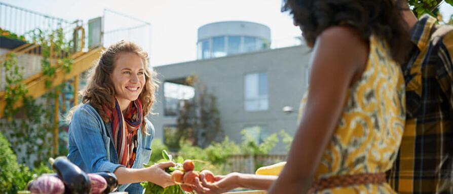 Friendly woman handing vegetables to a couple