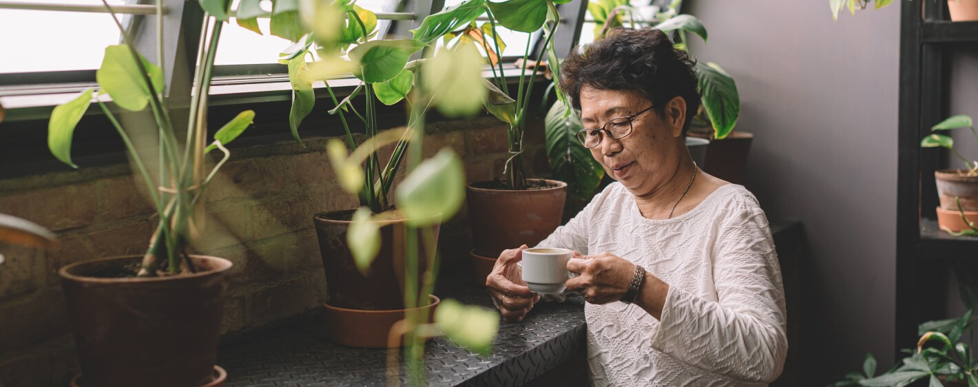 A person having a coffee break surrounded by plants
