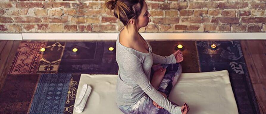 Young woman meditating at home in lotus yoga pose
