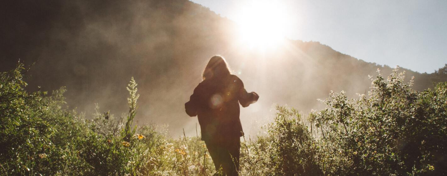 woman running towards light surrounded by foliage and mountains