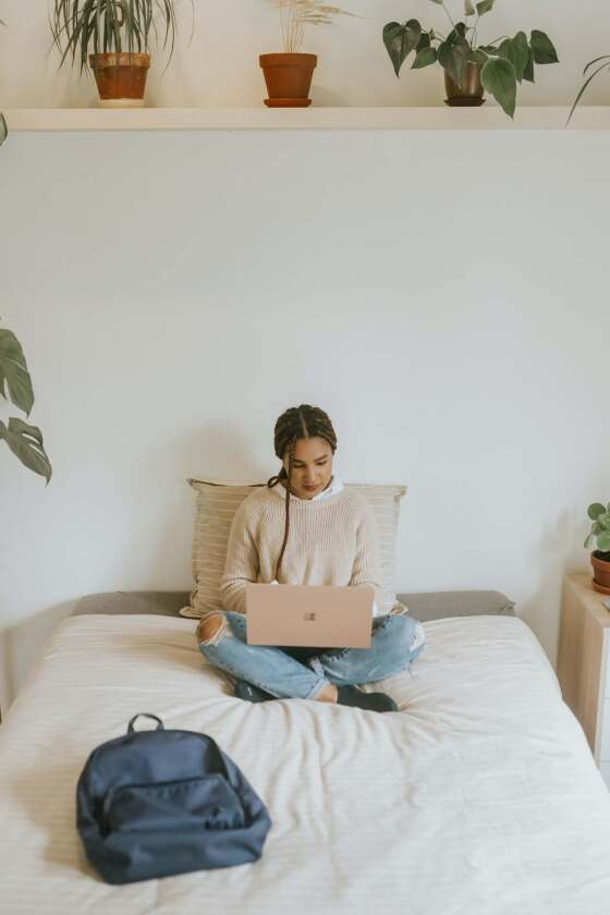 Woman sitting at her bed using her laptop