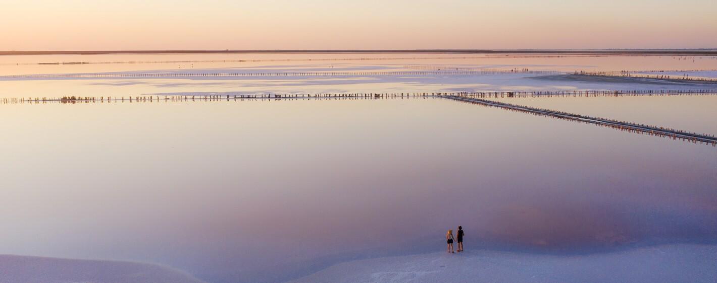 Scenic aerial view of two people walking on  pink salt lake