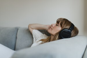 Woman listening to music  during coronavirus quarantine on a couch