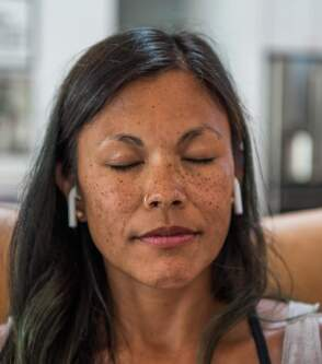 A woman sitting at her couch with eyes closed listening to meditation