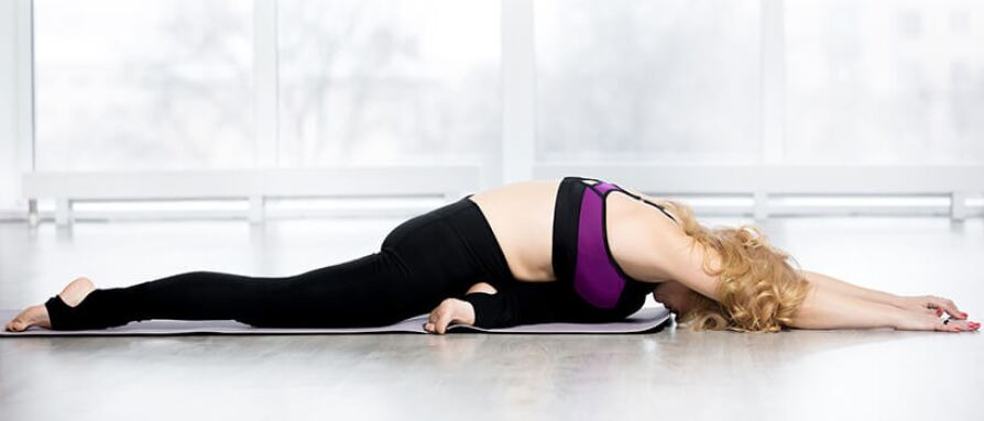 Woman in sleeping swan yoga pose