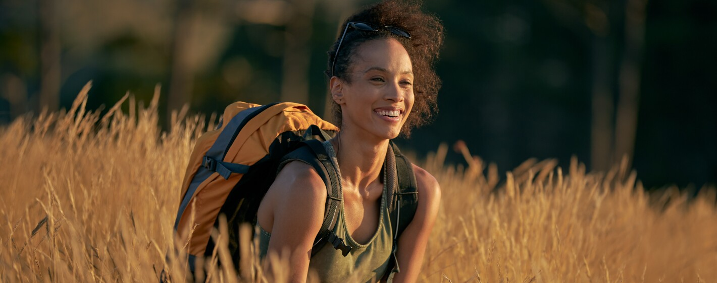 Woman with backpack smiling in field