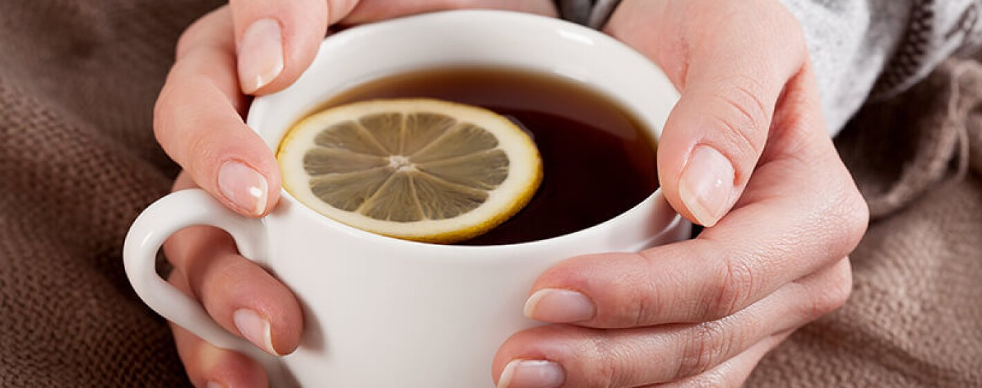 Woman holding a cup of tea with lemon