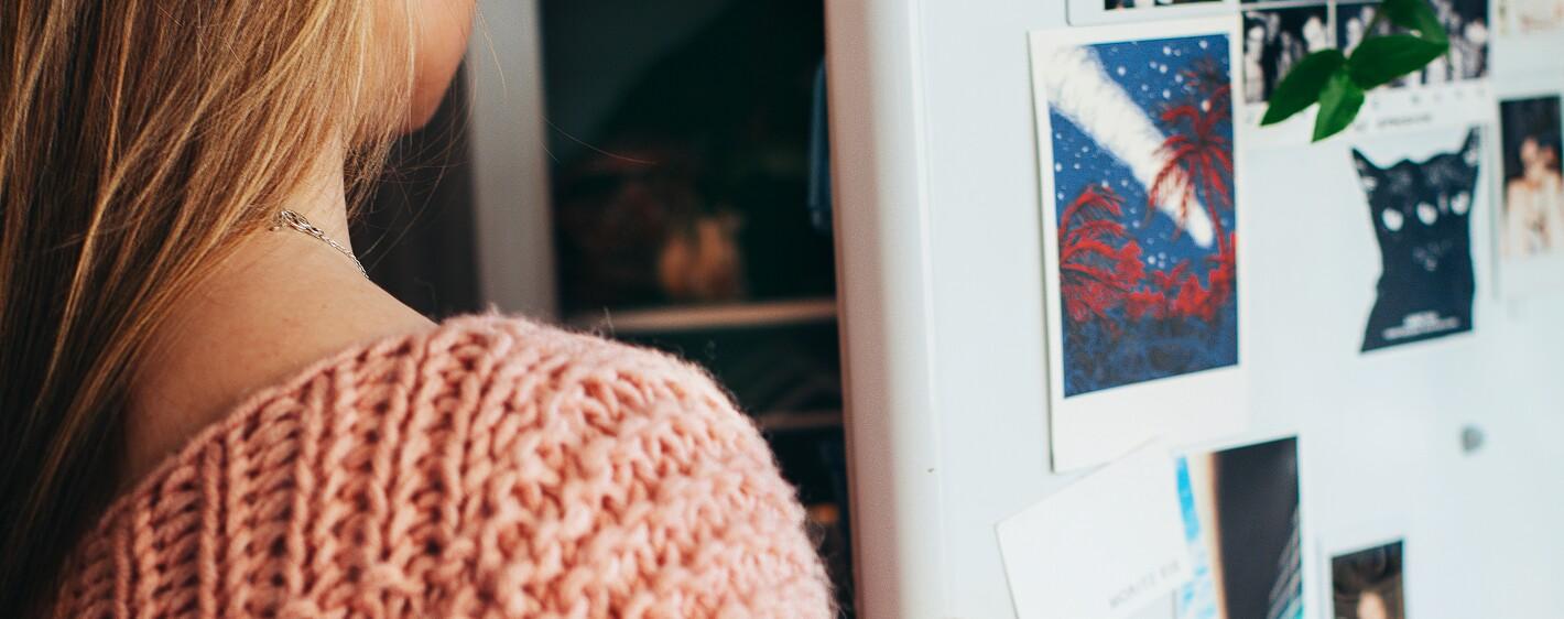 Woman wearing pink knit top refrigerator