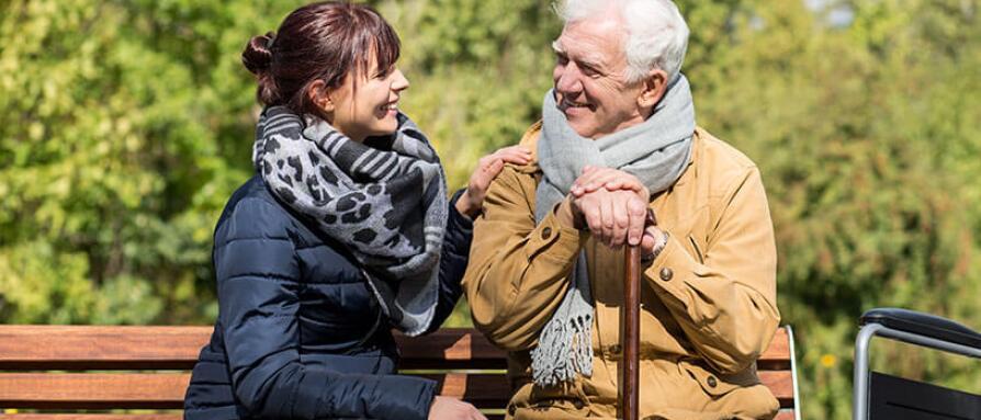 caretaker enjoying afternoon on bench with older gentleman