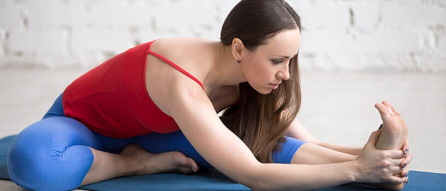 A young woman in head-to-knee forward bend yoga pose (Janu Sirsasana)