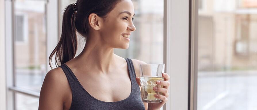 woman drinking lemon water post workout