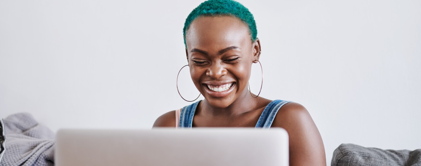 Smiling woman on sofa with laptop