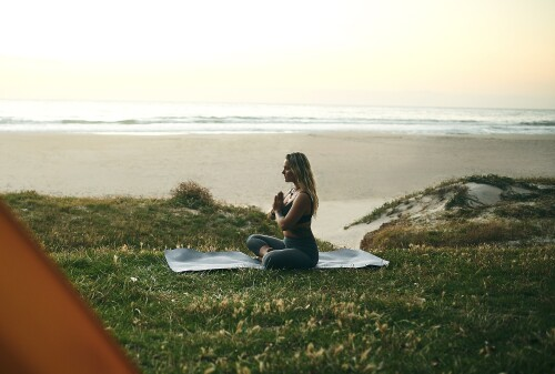 Full length shot of an attractive young woman sitting alone and meditating during a relaxing day outdoors
