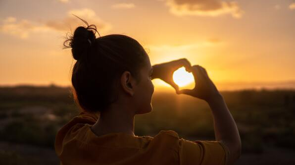 A young woman framing the sunset with her hands