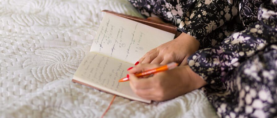 woman journaling in bed