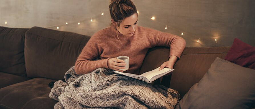 woman relaxing on couch reading book drinking tea