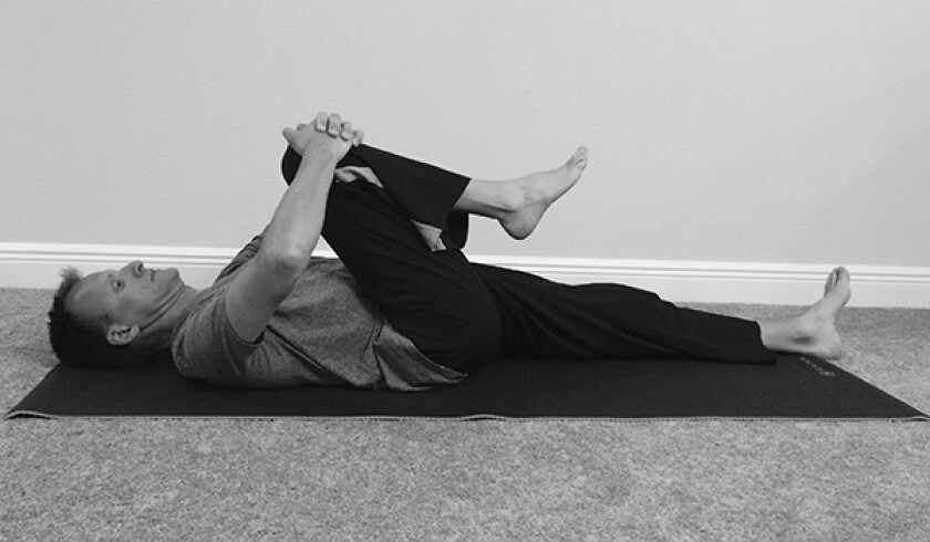 Man in knee to chest yoga pose