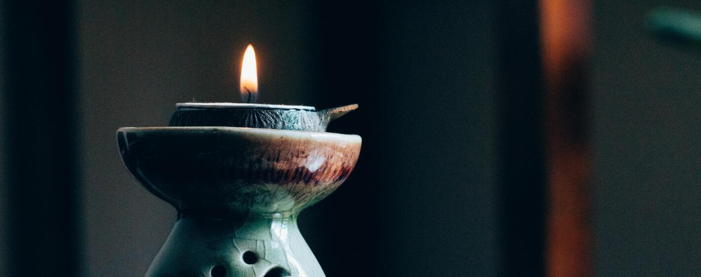 A lit candle on a beautiful stand