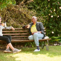 Laughing senior friends sitting together on a park bench