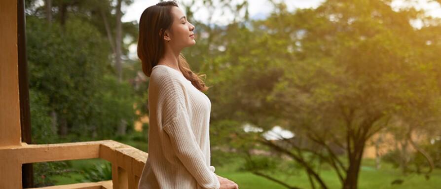 woman breathing outside cabin balcony