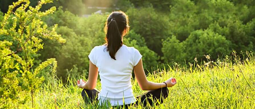 A young woman meditating in nature