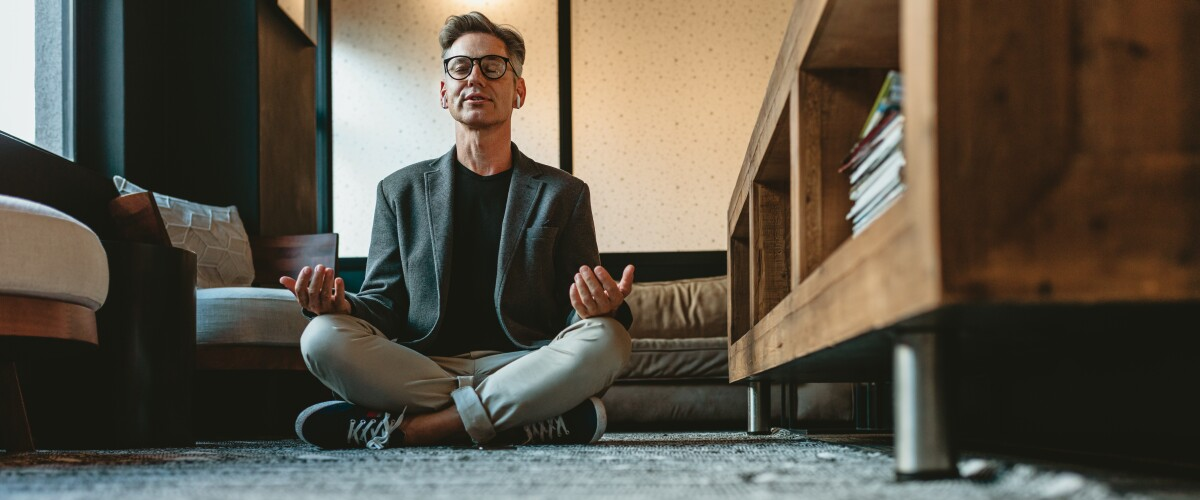 Mature businessman doing yoga meditation in office lounge