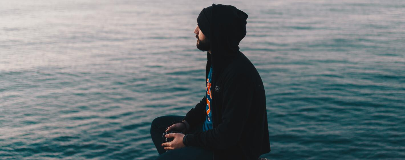Guy in a hoodie sitting on a rock at the beach