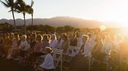 A group of people sitting in chairs meditating with their eyes closed