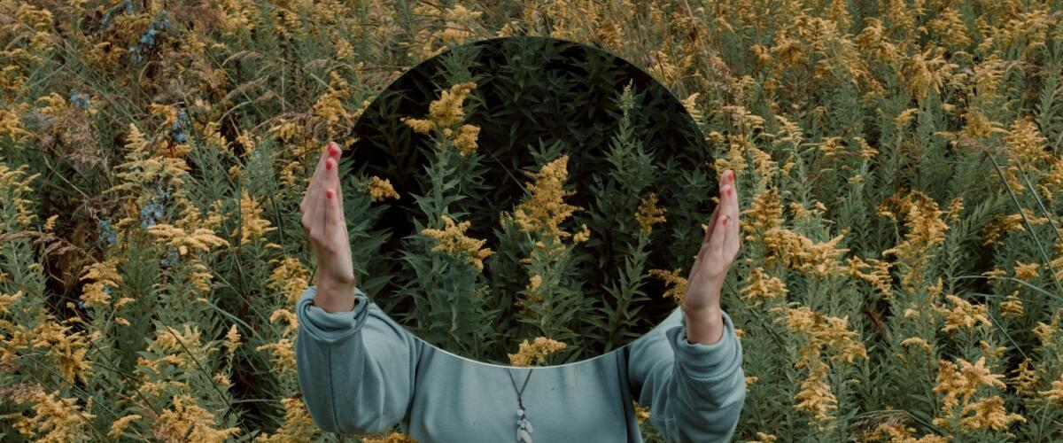 Girl in field holding mirror