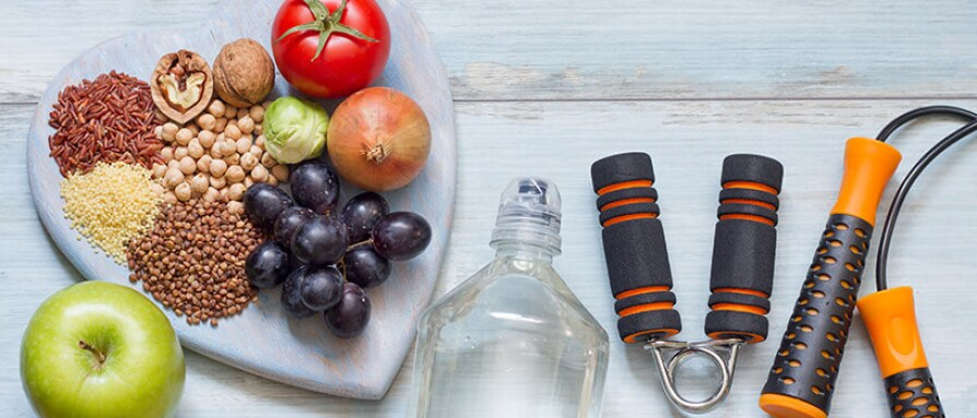 A variety of healthy grains, nuts, seeds, vegetables, fruit and exercise equipment on a wooden table
