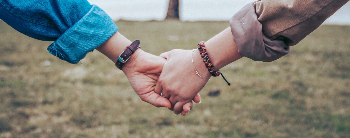 A close up of two friends holding hands