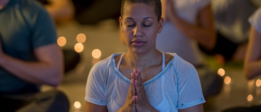 woman in candlelit meditation class