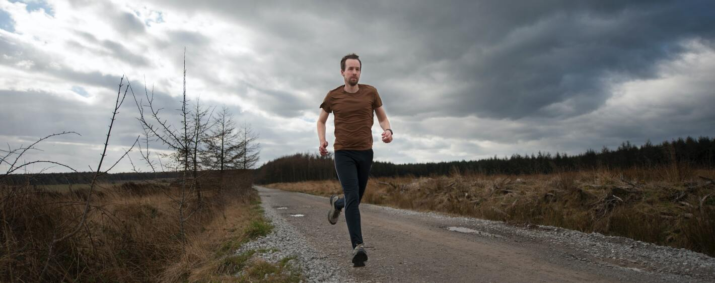 Guy running with cloudy sky
