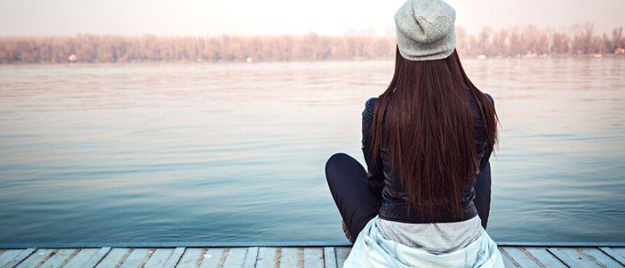 woman sitting near a lake