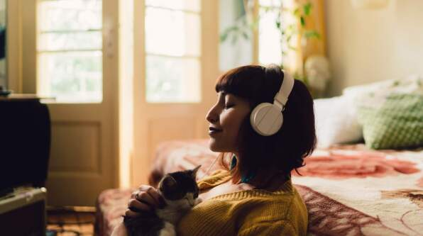 A young woman sitting listening to meditation and holding a kitten