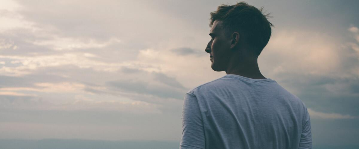 Guy in a white t-shirt looking out at mountains