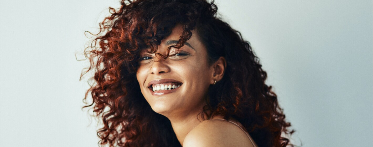 Girl with curly red hair smiling