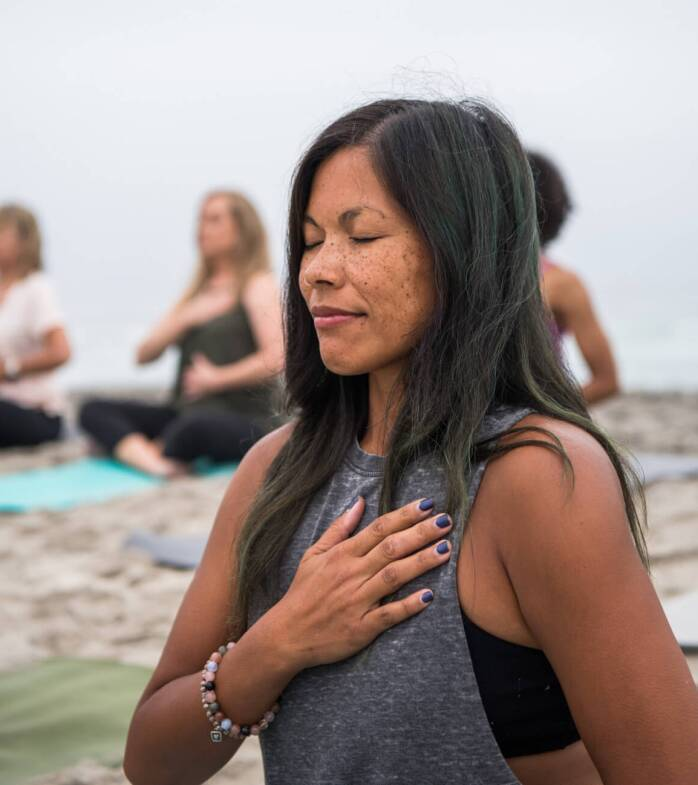 Woman meditating with hand over her heart