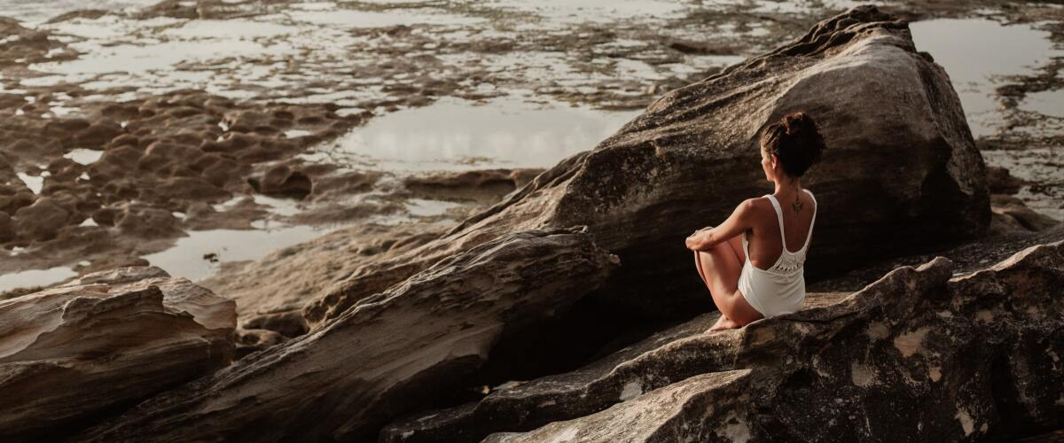 A young woman sitting on a rock by the ocean