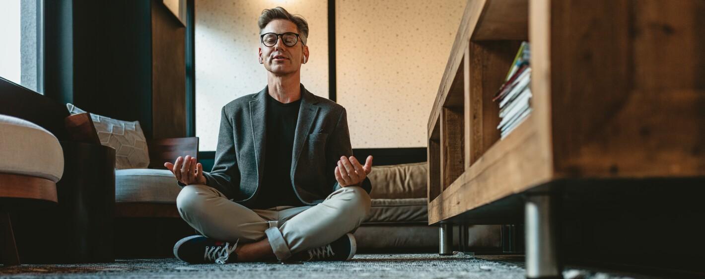 Mature businessman doing yoga meditation in office lounge