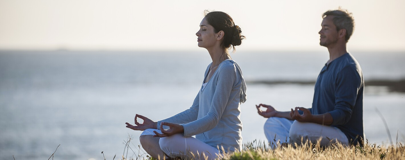 handsome couple practicing meditation exercises on the beach at