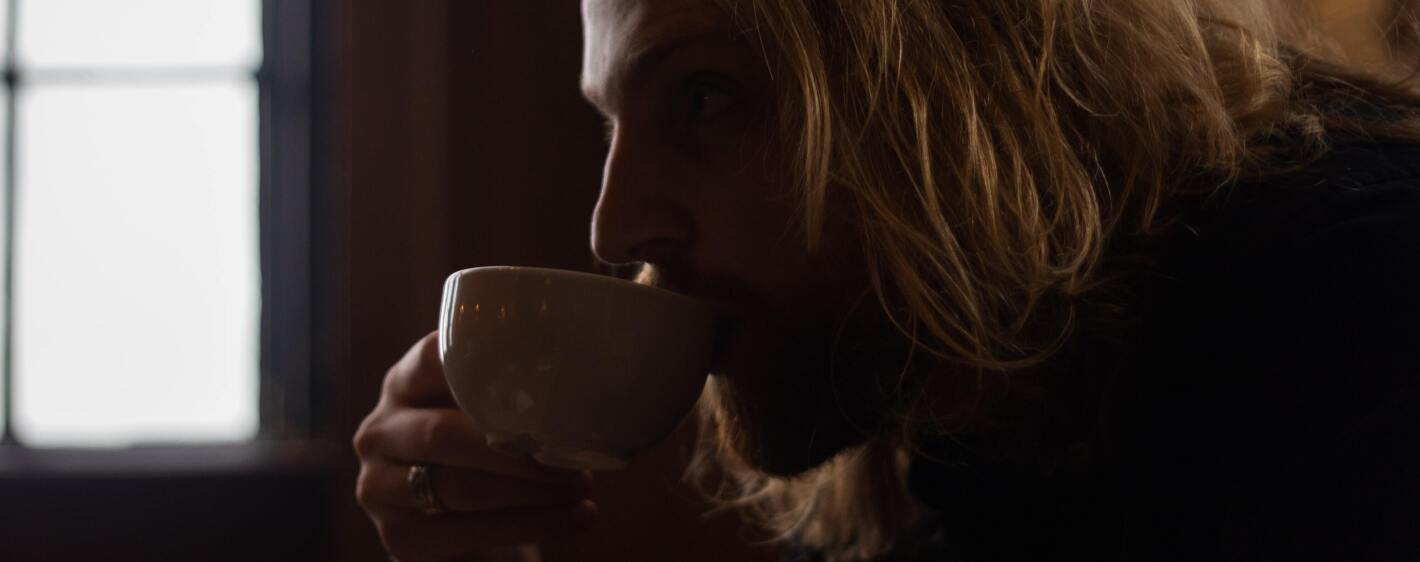 A man sipping on a cup of tea