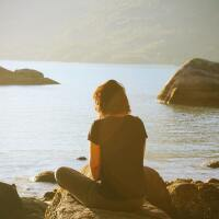 Woman sitting on rock looking out over a bay