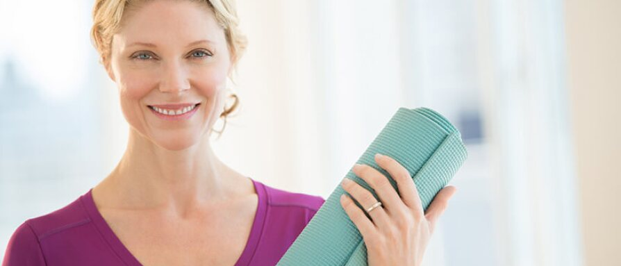 woman smiling with yoga mat