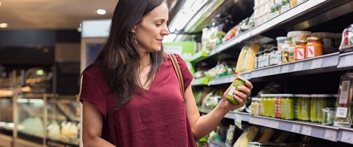 woman checking label at grocery store