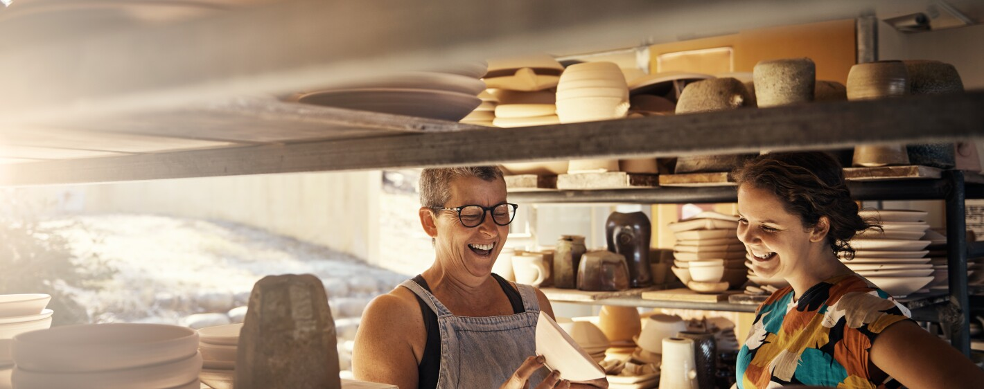 Potter and customer laughing in pottery studio
