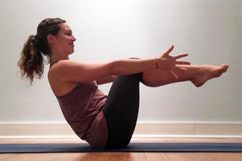 Yoga teacher in boat pose