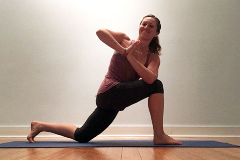 Yoga teacher in supported revolved lunge pose