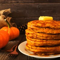 Stack of fall pumpkin spice breakfast pancakes with caramel sauce. Side view table scene against dark wood.