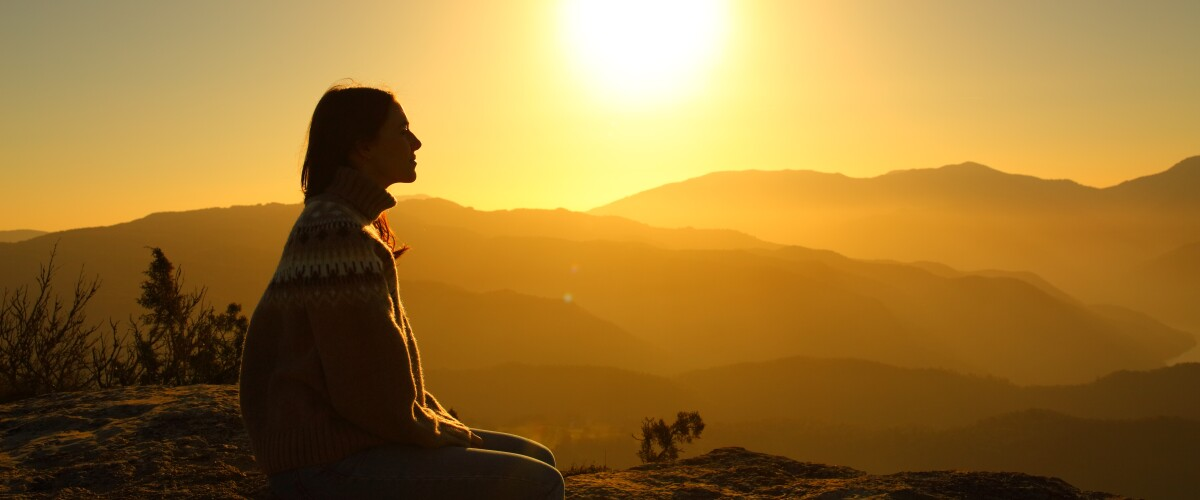 Silhouette of a woman contemplating nature at sunset